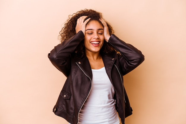 베이지 색 배경에 고립 된 젊은 아프리카 계 미국인 여자는 즐겁게 손을 머리에 유지 웃음. 행복 개념.