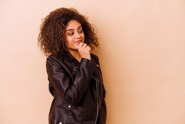베이지 색 배경에 고립 된 젊은 아프리카 계 미국인 여자 복사본 공간을보고 뭔가 대해 생각을 편안 하 게.