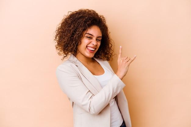 指でロックジェスチャーを示すベージュの背景に分離された若いアフリカ系アメリカ人女性