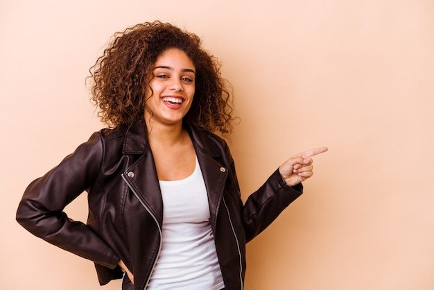 人差し指を離れて元気に指しているベージュの背景に分離された若いアフリカ系アメリカ人の女性。