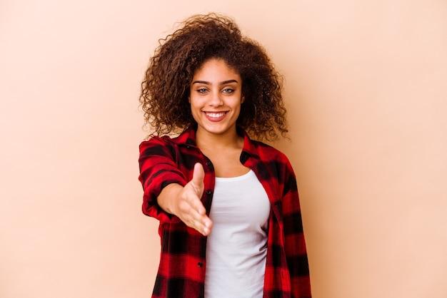 인사말 제스처에 카메라에 손을 스트레칭 베이지 색 배경에 고립 된 젊은 아프리카 계 미국인 여자.