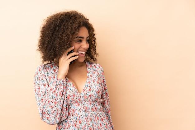 Молодая афроамериканская женщина изолирована на бежевом, ведя разговор с мобильным телефоном с кем-то