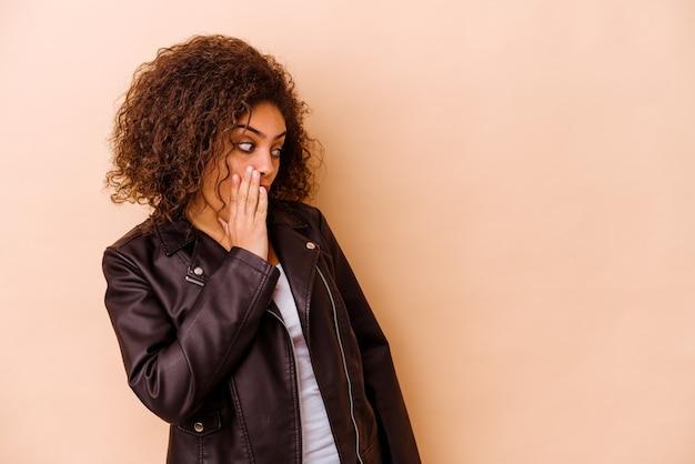Молодая афро-американская женщина, изолированная на бежевой стене, шокирована из-за чего-то, что она видела.