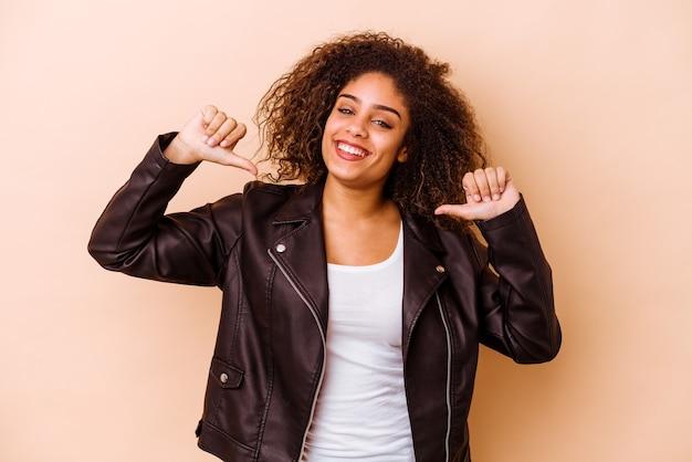 ベージュの壁に隔離された若いアフリカ系アメリカ人の女性は、誇りと自信を持って、従うべき例を感じます