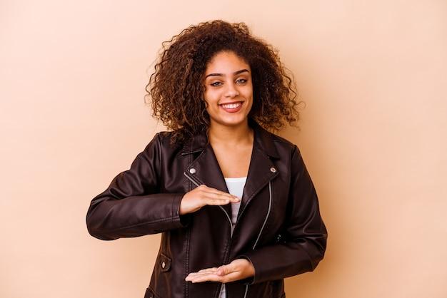 Молодая афро-американская женщина, изолированные на бежевой стене, держа что-то обеими руками, презентация продукта.