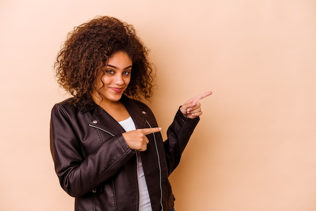 흥분과 욕망을 표현하는 복사 공간에 집게 손가락으로 가리키는 베이지 색 벽에 고립 된 젊은 아프리카 계 미국인 여자