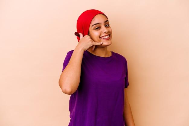 指で携帯電話の呼び出しジェスチャーを示すベージュの壁に分離された若いアフリカ系アメリカ人女性。
