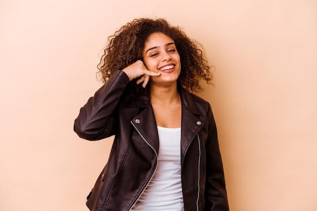 손가락으로 휴대 전화 제스처를 보여주는 베이지 색 벽에 고립 된 젊은 아프리카 계 미국인 여자