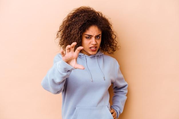 ベージュの壁に孤立した若いアフリカ系アメリカ人の女性は、猫を模倣した爪、攻撃的なジェスチャーを示しています。