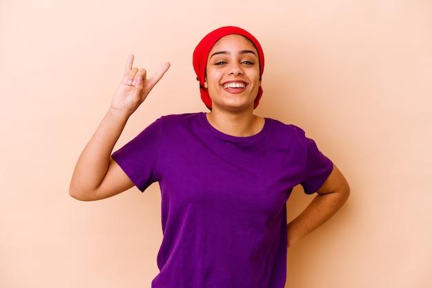 Молодая афро-американская женщина изолирована на бежевой стене, показывая рок-жест пальцами