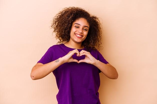 웃 고 손으로 심장 모양을 보여주는 베이지 색 벽에 고립 된 젊은 아프리카 계 미국인 여자