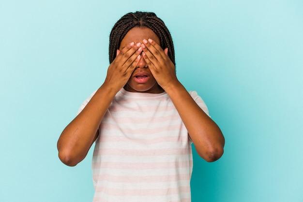 Молодая афро-американская женщина, изолированная на синем фоне, боится, закрывая глаза руками.