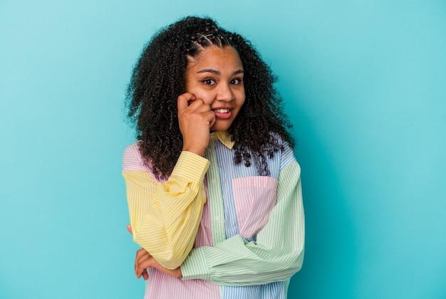 Молодая афро-американская женщина, изолированная на синем фоне, кусает ногти, нервничает и очень тревожится.
