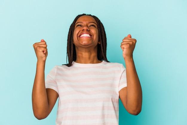 勝利、情熱と熱意、幸せな表現を祝う青い背景で隔離の若いアフリカ系アメリカ人女性。
