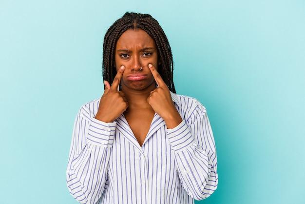Молодая афро-американская женщина изолирована на синем фоне плачет, недовольна чем-то, агонией и концепцией замешательства.