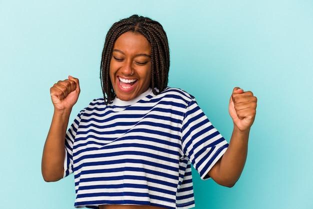 Молодая афро-американская женщина, изолированные на синем фоне, танцы и развлечения.