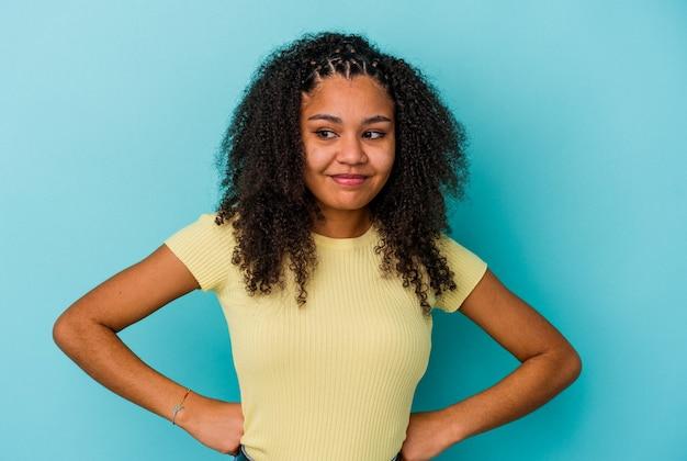 목표와 목적을 달성하는 꿈을 꾸고 파란색 배경에 고립 된 젊은 아프리카 계 미국인 여자