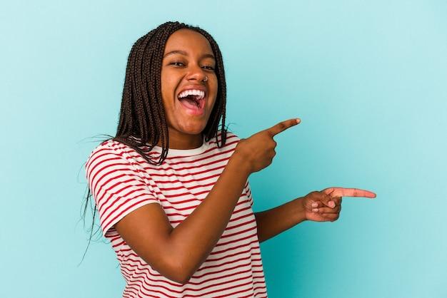 青い背景に孤立した若いアフリカ系アメリカ人の女性は、離れて人差し指を指して興奮しました。
