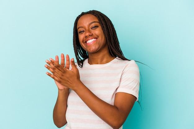 Молодая афро-американская женщина, изолированная на синем фоне, чувствуя себя энергичной и комфортной, уверенно потирая руки.