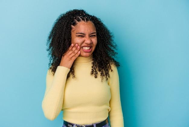 強い歯の痛み、臼歯の痛みを持っている青い背景で隔離の若いアフリカ系アメリカ人女性。