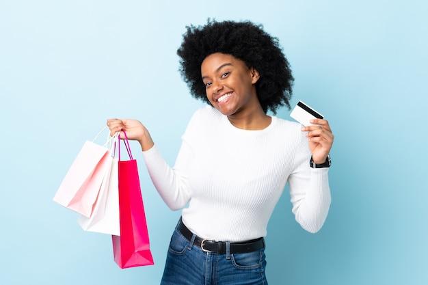 쇼핑백과 신용 카드를 들고 파란색 배경에 고립 된 젊은 아프리카 계 미국인 여자