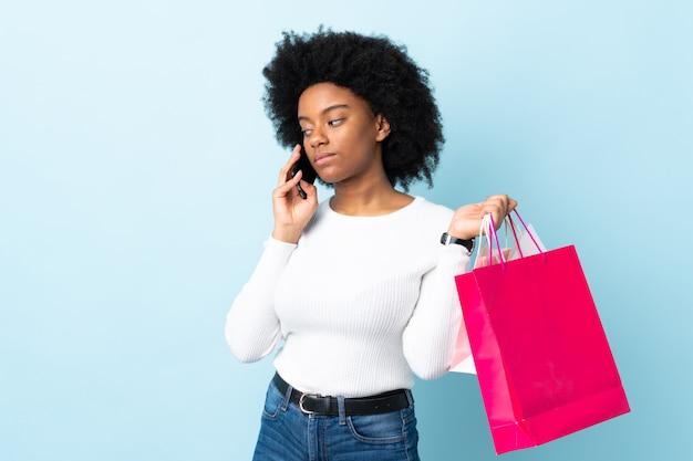 Молодая афро-американская женщина изолированная на голубой предпосылке держа хозяйственные сумки и вызывая друга с ее сотовым телефоном