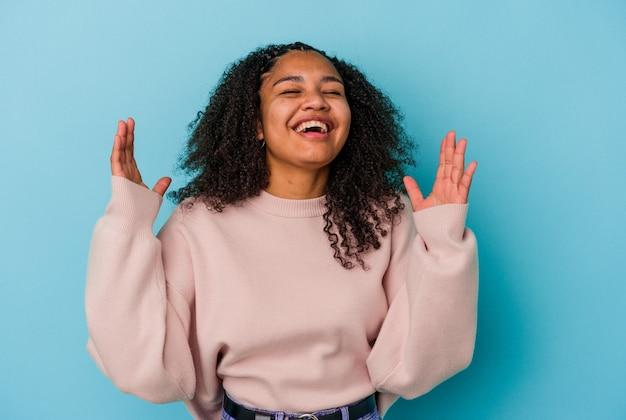 파란색 배경에 고립 된 젊은 아프리카 계 미국인 여자는 큰 소리로 가슴에 손을 유지 웃음.