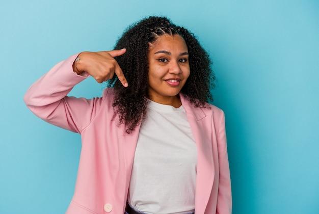 자랑스럽고 자신감이 셔츠 복사 공간을 손으로 가리키는 파란색 배경 사람에 고립 된 젊은 아프리카 계 미국인 여자