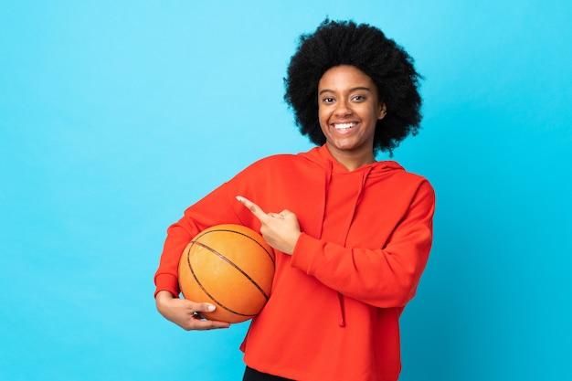 バスケットボールをし、側面を指している青い背景で隔離の若いアフリカ系アメリカ人女性