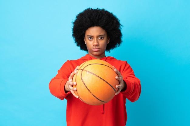 バスケットボールをしている青い背景で隔離の若いアフリカ系アメリカ人女性