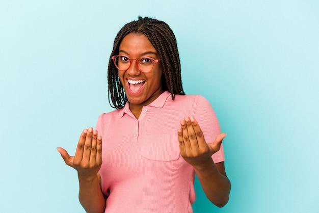 誘うようにあなたに指で指している青い背景に孤立した若いアフリカ系アメリカ人の女性が近づいています。