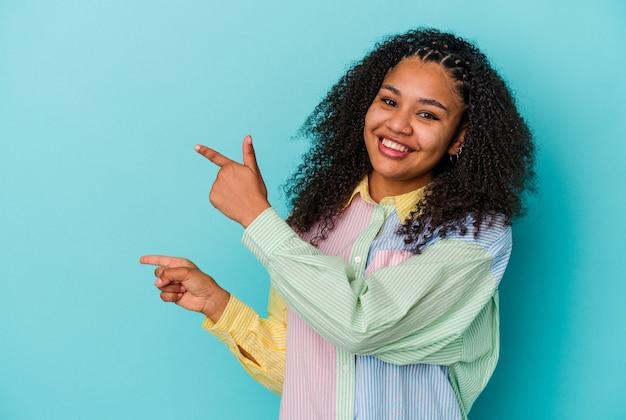 青い背景に若いアフリカ系アメリカ人女性が、人差し指でコピー スペースを指し、興奮と欲求を表現しています。