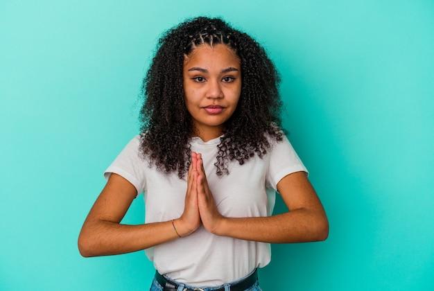 青の背景に若いアフリカ系アメリカ人女性が祈り、献身を示し、神のインスピレーションを求める宗教家。