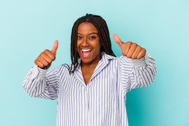 若いアフリカ系アメリカ人の女性は、青い背景に孤立し、両方の親指を上げて、笑顔で自信を持っています。