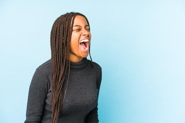 Молодая афро-американская женщина, изолированная на синем фоне, кричит в сторону копии пространства