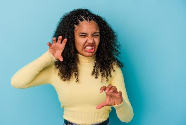 猫を模倣した爪、攻撃的なジェスチャーを示す青い背景に分離された若いアフリカ系アメリカ人の女性。