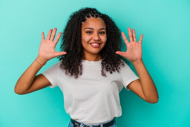 青の背景に分離された若いアフリカ系アメリカ人の女性は、手で10番を示しています。