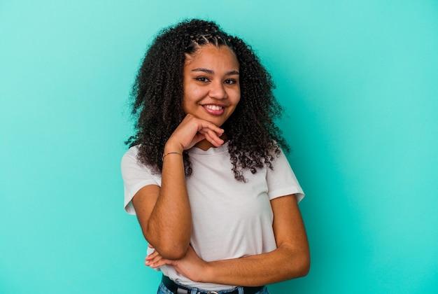행복 하 고 자신감, 손으로 턱을 만지고 웃 고 파란색 배경에 고립 된 젊은 아프리카 계 미국인 여자.
