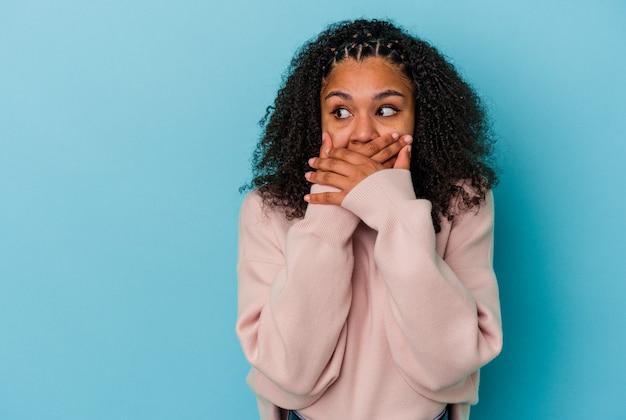 파란색 배경에 고립 된 젊은 아프리카 계 미국인 여자 손으로 입을 덮고 복사 공간을 찾고 사려 깊은.