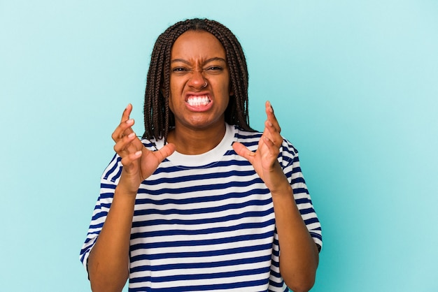 青い背景に孤立した若いアフリカ系アメリカ人の女性は、緊張した手で叫んで動揺します。