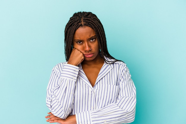 コピースペースを見て、悲しくて物思いにふける青い背景に孤立した若いアフリカ系アメリカ人の女性。