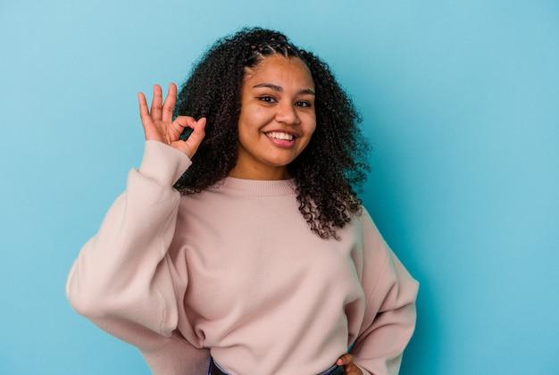 파란색 배경에 고립 된 젊은 아프리카 계 미국인 여자는 눈을 윙크 하 고 손으로 괜찮아 제스처를 보유하고있다.