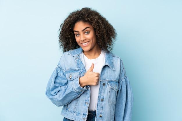 ジェスチャー親指を与える青に分離された若いアフリカ系アメリカ人女性