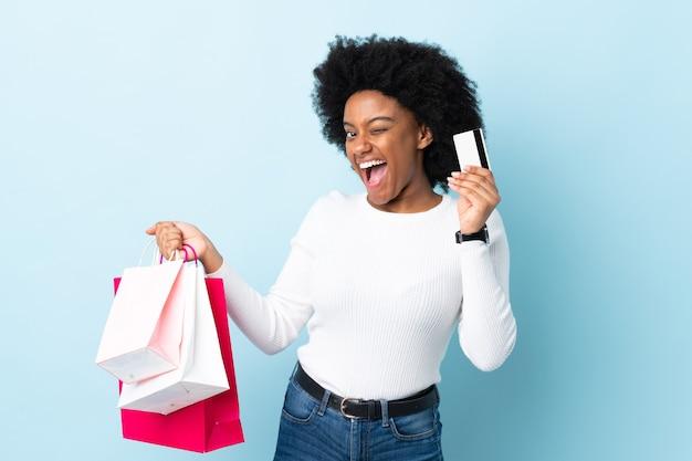 ショッピングバッグとクレジットカードを保持している青に分離された若いアフリカ系アメリカ人女性