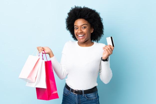 Молодая афро-американская женщина изолирована на синем, держа сумки и кредитную карту