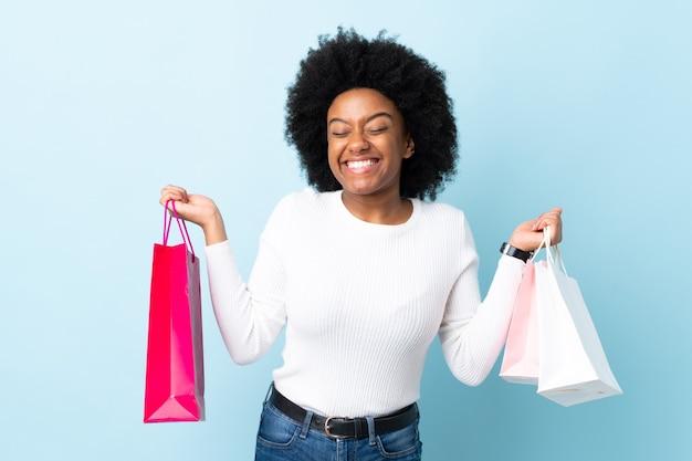 買い物袋を押しながら笑みを浮かべて青に分離された若いアフリカ系アメリカ人女性