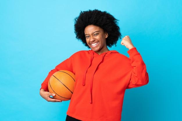 Молодая афро-американская женщина изолирована на синем, играет в баскетбол и гордится собой