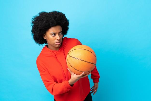 Молодая афро-американская женщина изолирована на синем, играя в баскетбол