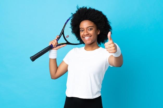 Молодая афро-американская женщина изолирована на синем, играя в теннис и с пальцем вверх