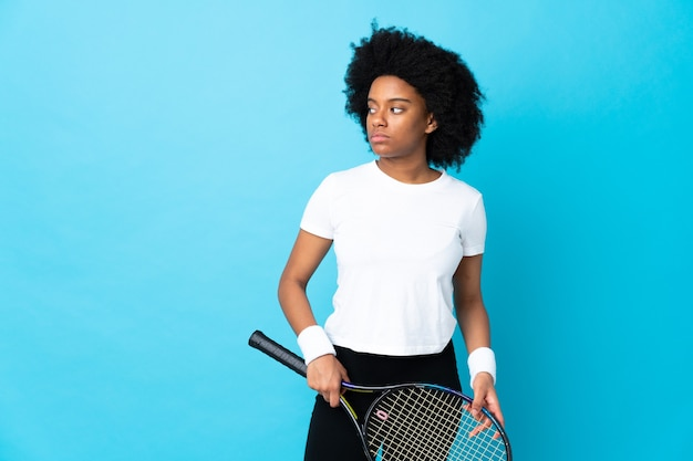 Молодая афро-американская женщина изолирована на синем, играя в теннис